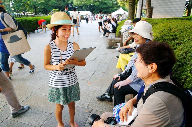 平和公園で取材をする新田冬和さん=6日夕、広島市中区、宮崎園子撮影