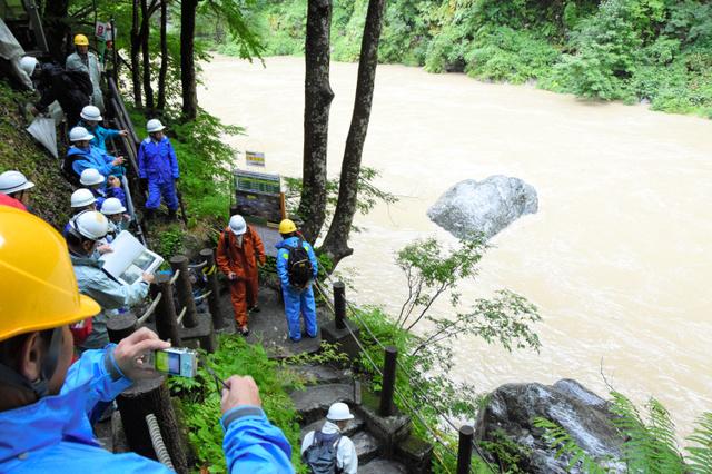 鐘釣温泉で、水没した河原露天風呂付近を視察する県職員ら。台風10号の影響で黒部川は濁流になっていた=黒部市