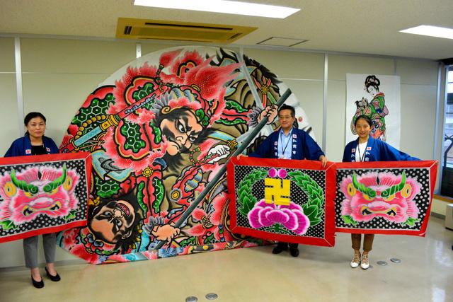 ふるさと納税の寄付者に贈る鏡絵と見送り絵を背に牡丹図を持つ市職員3人=弘前市役所