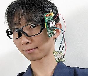 コンピューターキットなどが装着できる鯖江式の新しいメガネをかけた福野さん。これをさらに進化させ、ウェアラブル端末に応用できないか開発中だ