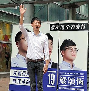 2日、駅前で支持を求める本土派「青年新政」の梁頌恒さん。後ろは「香港を取り戻す 時代革命」のスローガン=香港