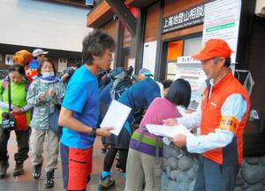 登山者から登山届を受け取る登山相談員の今川剛之さん(右)=8月、長野県松本市の上高地