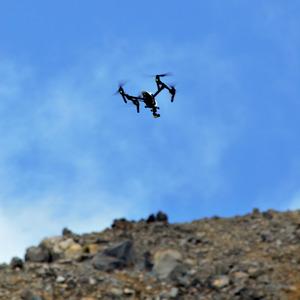 御嶽山山頂近くの谷の上空から尾根に向かって飛行するドローン=木曽町