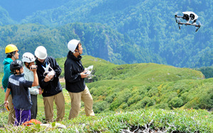 行方不明者の手がかりを得ようと、撮影のためにドローンを飛ばす関係者たち=3日午前11時25分、長野県木曽町の御嶽山