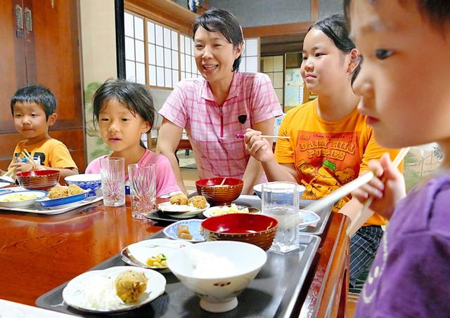 高橋さん(中央)と一緒に食卓を囲み、ご飯を食べる子どもたち=三島市佐野