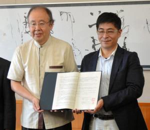 協定書を手に持つ原田理事長(右)と佐々木副知事=県庁