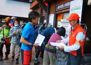 登山者から登山届を受け取る登山相談員の今川剛之さん=8月11日、長野県松本市の上高地