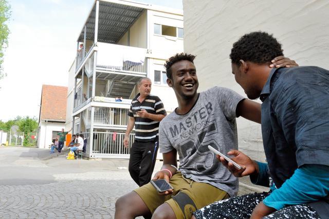 ドイツ・バイエルン州ツィルンドルフの難民レセプションセンター内は、青年らがスマートフォンで遊びながらじゃれ合うのどかさだ=喜田尚撮影