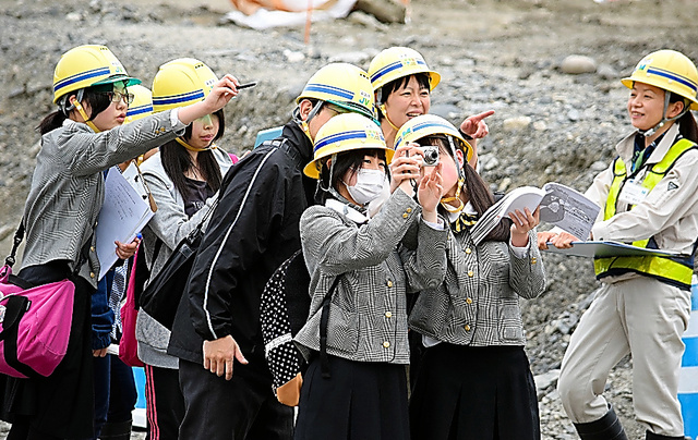 盛り土中の市街地を撮影し、定点観測する大槌高校復興研究会の生徒たち=5月、岩手県大槌町