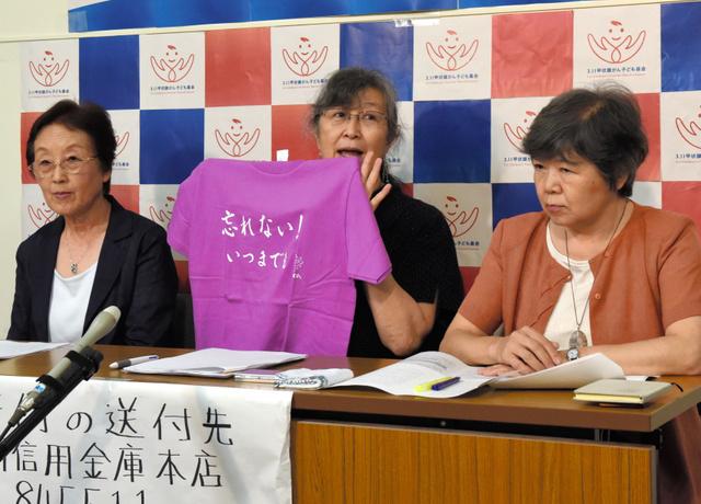 「忘れない!いつまでも」。基金の賛同人になった吉永小百合さん直筆のTシャツを掲げる武藤類子・副代表理事(中央)。資金集めのために販売するという=9日、福島県庁、本田雅和撮影