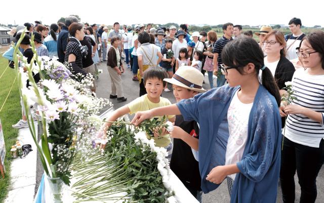 新しく造られた堤防の上に設置された献花台に花を手向ける住民ら=10日午後0時47分、茨城県常総市、竹花徹朗撮影