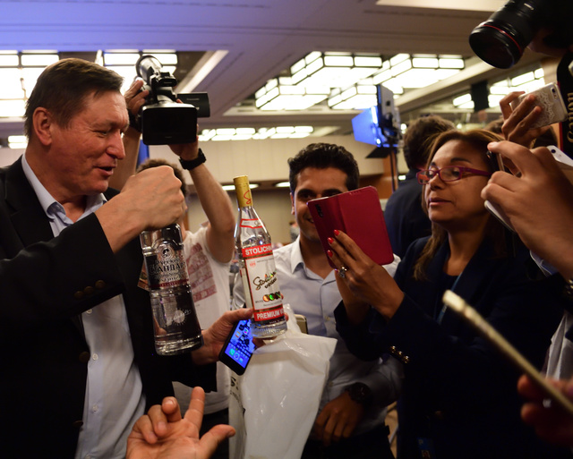 ロシアのラブロフ外相が記者団に届けたウォッカを手に取って、各国の記者に銘柄などを説明するロシア大手通信社の特派員(左)=9日夜、スイス・ジュネーブ市内、松尾一郎撮影