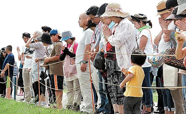 新しく造られた堤防の上で手を合わせる住民ら=10日午後、茨城県常総市、竹花徹朗撮影