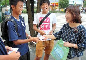 「憲法9条ティッシュ」を配る須藤道子さん(右)。大学生が立ち止まってくれた=9日、仙台市青葉区