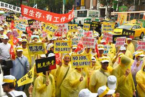 「観光惨業」などと書いたプラカードを掲げてデモ行進する台湾の観光業者ら=台北、12日、鵜飼啓撮影