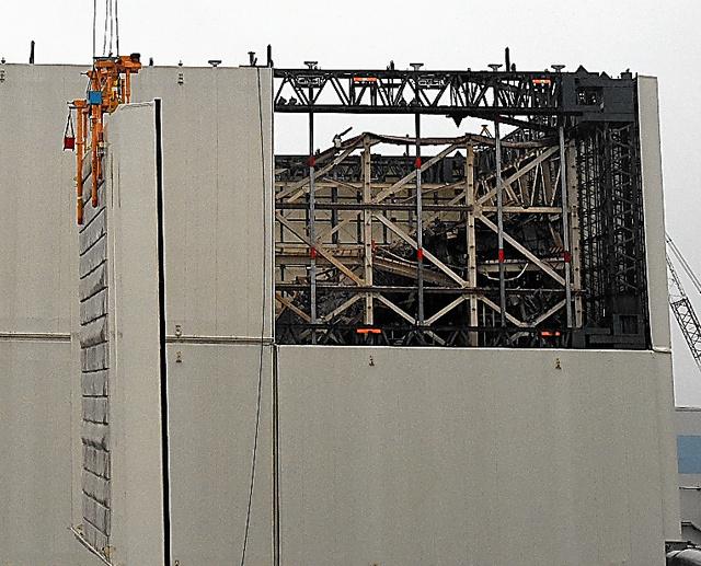 壁部分のカバーが外され、がれきがむき出しになった1号機の原子炉建屋=13日午前6時22分、福島県大熊町の東京電力福島第一原発、代表撮影
