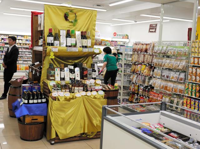 セブン―イレブン川崎登戸駅前店の酒売り場。木製の棚や樽(たる)の上にワインやウイスキーが並び、生ハムやチーズなども一緒に売られている=川崎市多摩区
