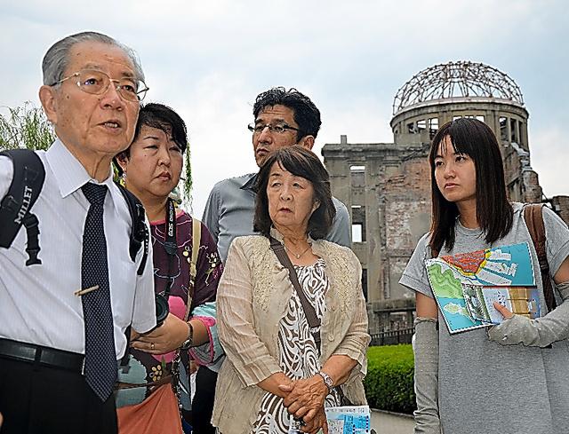 視察に訪れた広島市の原爆ドームの前で原田浩さん(左端)の言葉に聴き入る佐藤美香さん(右端)