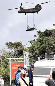 大型車両を運搬する自衛隊ヘリ=13日午前、沖縄県東村高江、沖縄タイムス提供