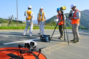 熊本地震で土砂崩れのあった阿蘇大橋周辺で、ドローンによる空撮の準備をする金沢大の調査チーム=熊本県南阿蘇村