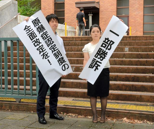 判決後、「一部勝訴」などと書かれた紙を掲げる原告側代理人弁護士=14日午前10時5分、名古屋地裁前