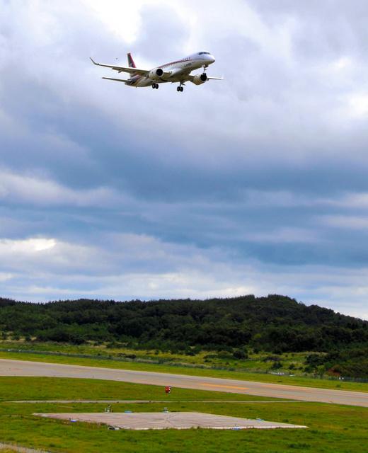 JAXAの飛行試験に協力するMRJ。滑走路脇にある木製の四角い台に設置されたマイクで騒音を測定した=輪島市三井町