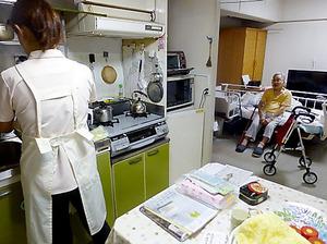 台所で調理するヘルパーに、好みのキャベツの切り方を伝える山田桂子さん(右)。電動ベッドや歩行器も暮らしに欠かせない=千葉市