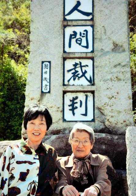 人間裁判の碑の前で記念撮影をした、在りし日の足立初枝さん(右)と井上久仁子さん=早島町早島、井上さん提供