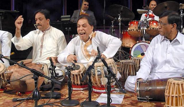 ニューヨークのジャズ・オーケストラ(奥)と、伝統楽器との掛け合いで観客を沸かせたタブラ奏者のバッルー・ハーン氏(中央)ら=2013年11月、映画配給会社サンリス提供