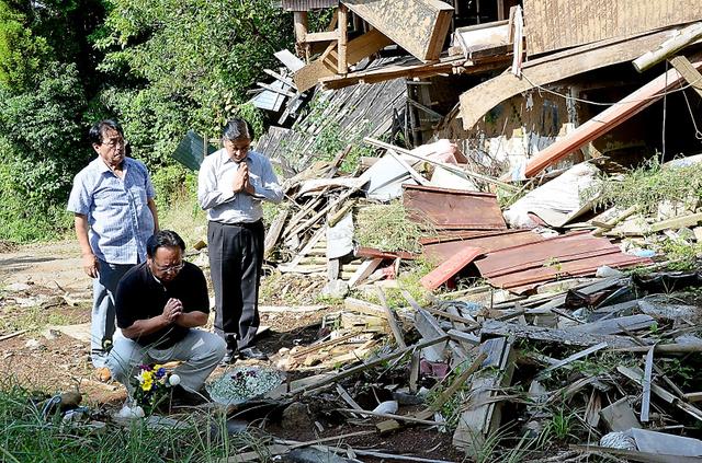 片島さん夫婦が亡くなった家の前で手を合わせる新所地区区長の山内博史さんら=16日、南阿蘇村