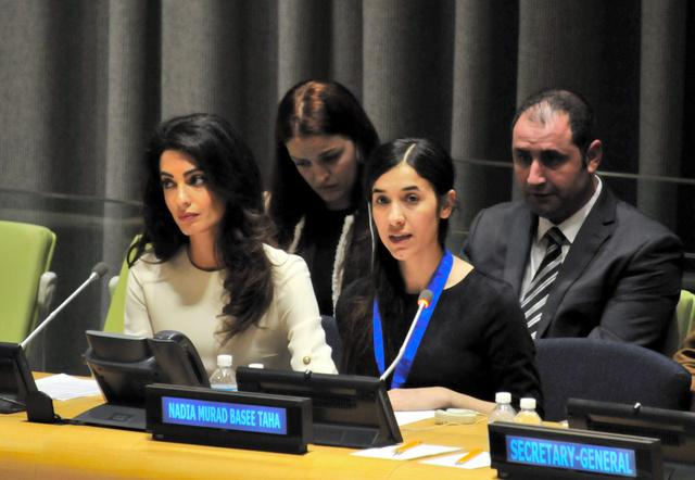 過激派組織「イスラム国」(IS)を裁きにかけることを求める少数派ヤジディ教徒のナディアさん(前列右)。言葉に詰まると、付き添った弁護士アマル・クルーニーさん(同左)が肩をさすっていた=16日、米ニューヨークの国連本部、金成隆一撮影