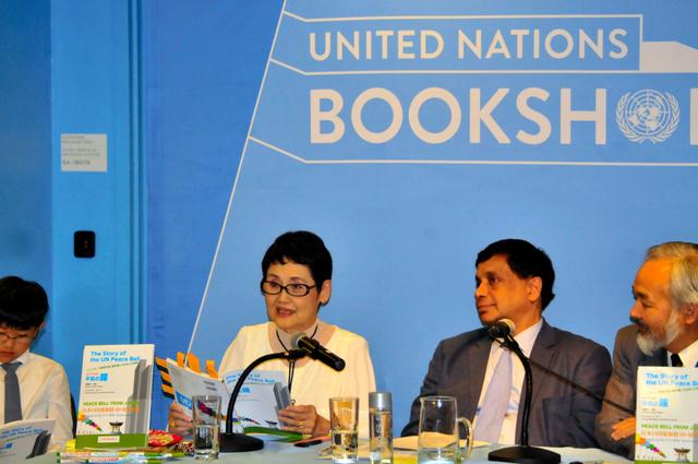出版記念会で絵本「コインでつなぐ平和の鐘」を朗読する高瀬聖子さん(中央)=16日、米ニューヨークの国連本部、金成隆一撮影