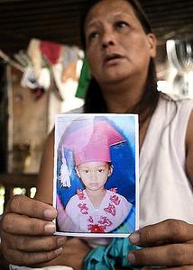 <巻き込まれた少女> ダニカちゃんの写真を持つ祖母のジェマさん=フィリピン・パンガシナン州ダグパン市