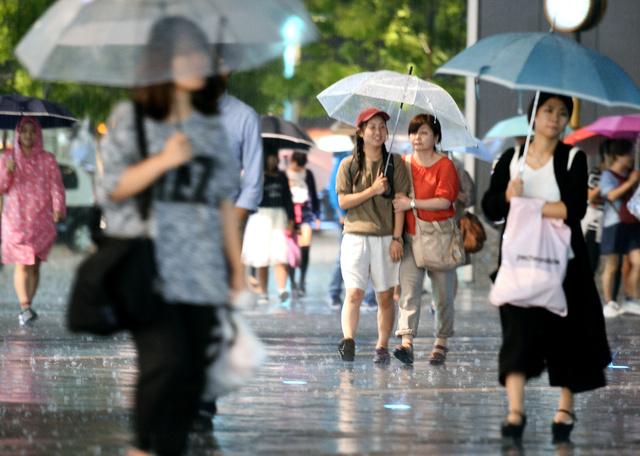 大粒の雨が降る中、博多駅へ向かう人たち=18日午後6時56分、福岡市博多区、久松弘樹撮影