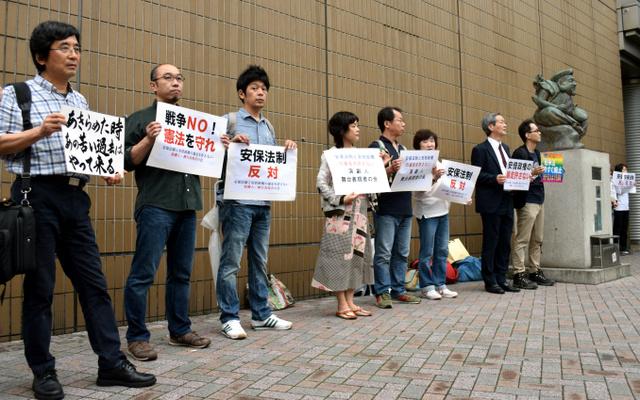 JR恵比寿駅前でサイレントスタンディングを行う鵜山仁さん(左)ら演劇人たち=東京都内
