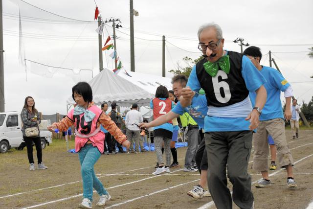 ピンポン球をスプーンで運ぶ「スプーンリレー」。大人も子どもも一緒に校庭を駆け回った=仙台市若林区