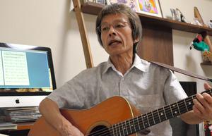 シンガー・ソングライターの宮沢勝之さん。できあがって間もない楽譜を前に、ギターを弾きながら歌う=清瀬市