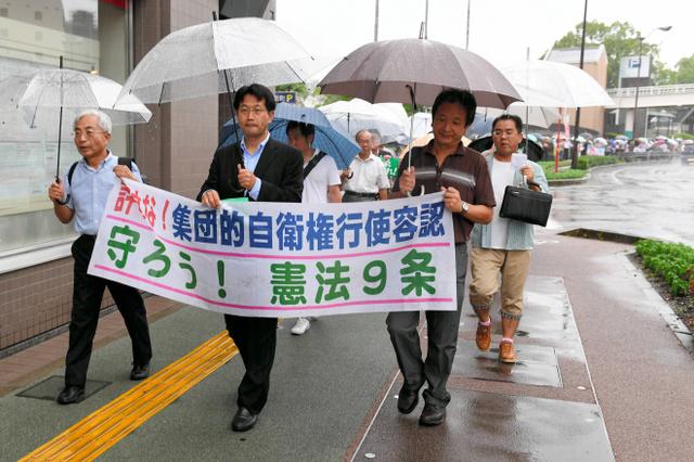 雨の中、安保関連法の廃止を求めて行進する人々=徳島市藍場町1丁目