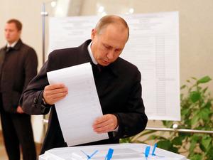 18日、モスクワでロシア下院選挙の投票をするプーチン大統領=ロイター