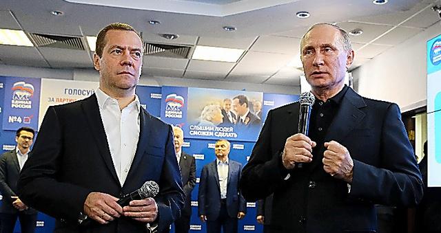 18日、モスクワにある与党「統一ロシア」の選対本部を訪れたプーチン大統領(右)とメドベージェフ首相=AFP時事