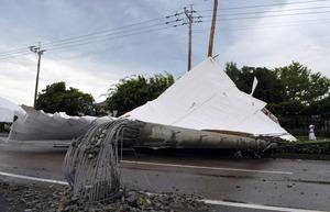 資材置き場の屋根が飛んで電柱をなぎ倒し、道路が通行止めとなった=20日午前7時20分、宮崎市阿波岐原町、伊藤秀樹撮影