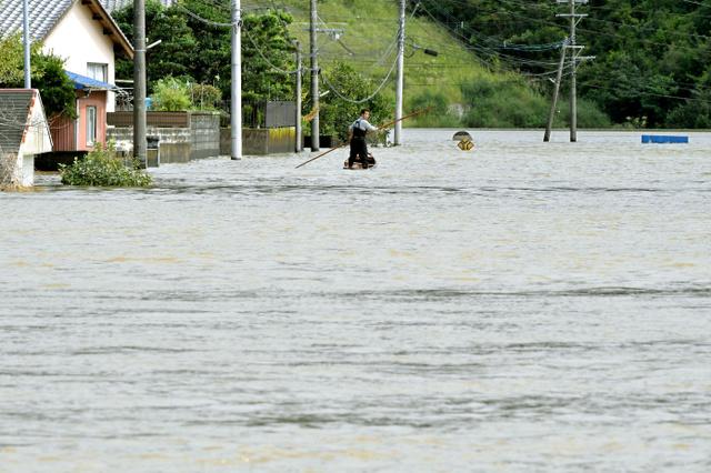 台風の影響で冠水し、道路標識が水没した場所で男性が小舟に乗って移動していた=20日午前10時59分、宮崎県延岡市、福岡亜純撮影