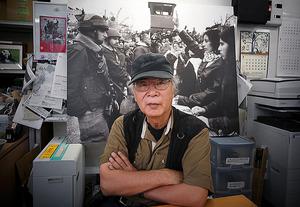 「DAYS JAPAN」の編集室で。後ろのパネルは、2002年にエルサレムで撮影した、イスラエル兵に抗議する女性たちの写真=東京都世田谷区、浅野哲司撮影