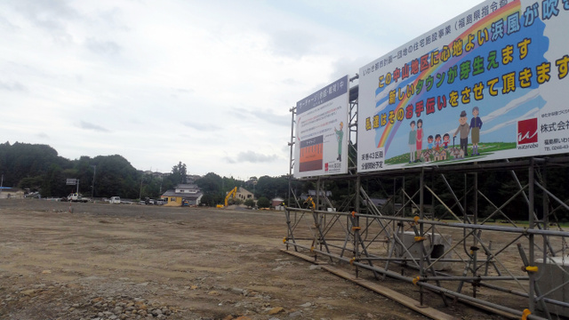 農地を宅地に転用する造成工事が進む。看板には来春分譲予定とある=16日、福島県いわき市