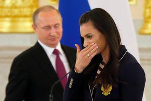 7月27日、リオ五輪ロシア選手団の壮行会でうつむく陸上女子棒高跳びの世界記録保持者エレーナ・イシンバエワ選手。左はプーチン大統領=ロイター。同選手は違反歴はないものの、ロシア陸上チームのドーピング問題で五輪に出場できなかった
