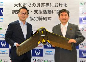 使用するドローンを手に協定を発表する古橋大地教授(左)と大木哲市長。=大和市役所