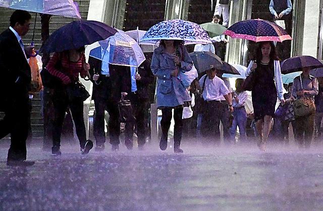 時折、雨が強く降るなか、足早に駅へ向かう人たち=20日午後、横浜市中区、恵原弘太郎撮影