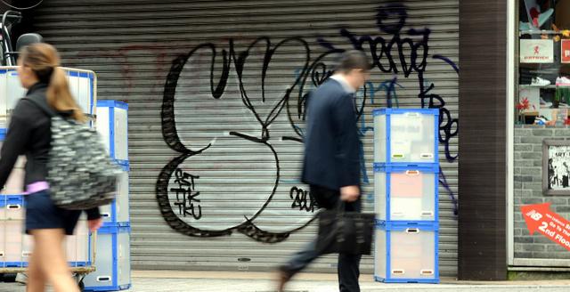 男に落書き(中央部分)された店舗のシャッター=21日午前、東京都渋谷区、池田良撮影