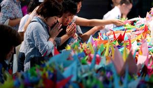 津久井やまゆり園の殺傷事件で亡くなった犠牲者を悼み、折り鶴を手向ける人たち=21日午後、横浜市中区、越田省吾撮影