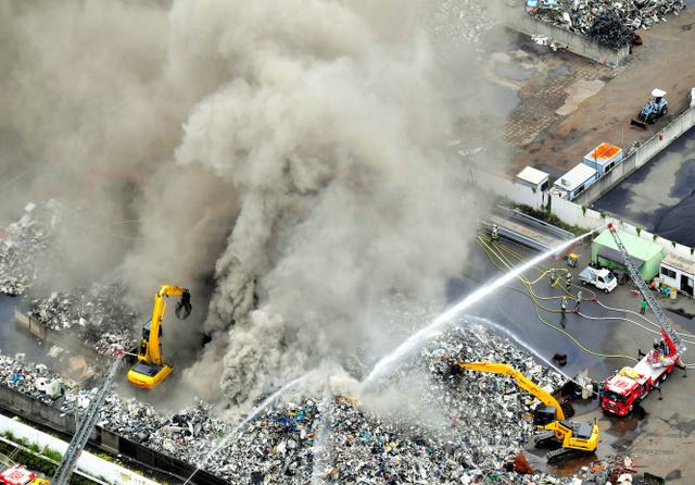 黒煙を上げて燃える廃材=22日午前10時53分、大阪市此花区、朝日新聞社ヘリから、高橋一徳撮影